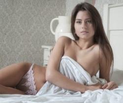 Проститутка лежит в кровати